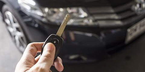Man hold car remote key for unlock or lock the black car in background.